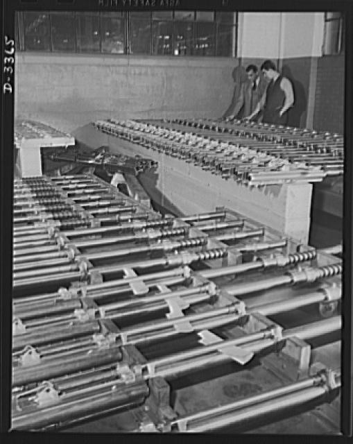 Twenty-millimeter machine guns for planes. American power in the air grows rapidly as machine guns of the finest quality pour from our production lines. These guns, entirely completed and ready to fire, await shipment from the large converted auto plant in which they were made. Oldsmobile, Lansing, Michigan