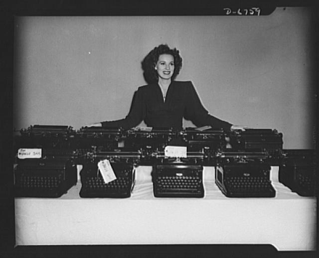 The stories they've told! Another load of RKO Radio typewriters is turned in to the government for war work. Somewhere in the lot is Maureen O'Harra's personal typewriter which she added to the pile before she would pose in the picture. The machines come from the script department where each one has played its role in recording countless memorable senes for screenplays. Taking time off between the shooting of scenes at the RKO Studios in Hollywood, Miss O'Harra helped collect more than seventy typewriters for future use by the Army, Navy, and Marines