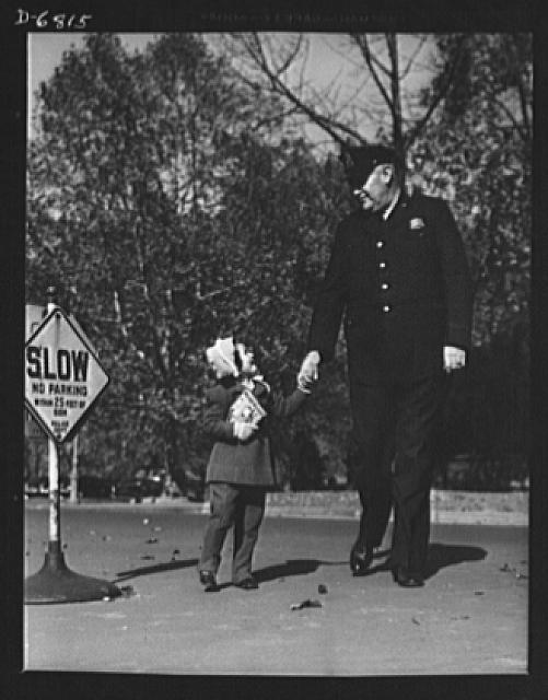 Thanksgiving, 1942. In America a uniform means protection, not persecution. This husky Washington, D.C. policeman is escorting a child across an intersection. Similar scenes can be duplicated in every community in free America