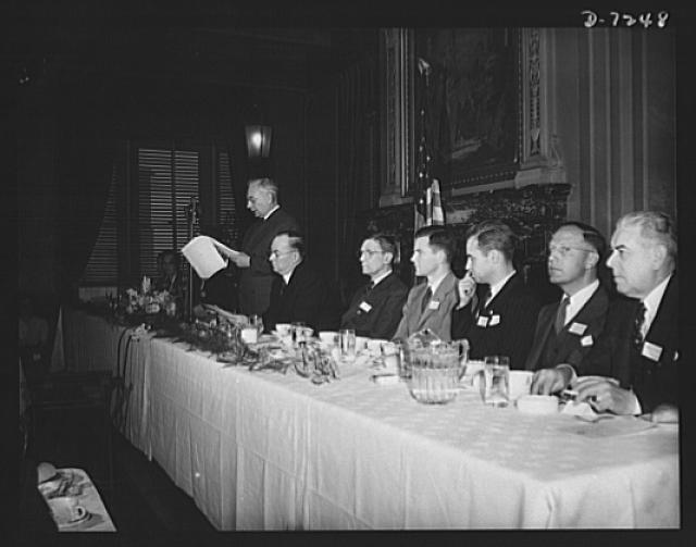 Citation winners. William G. Marshall, Director of the War Production Drive. Standing, is shown presenting the Honor Group at the luncheon tendered by Donald M. Nelson, Chairman of War Production Board (WPB), following the White House ceremony. Left to right: Mrs. Marshall, Mr. Nelson, Joseph H. Kautsky, Dodge Plant Link-Belt Company, Indianapolis, Indiana, James A. Merrill, research chemist with the Goodyear Tire and Rubber Company of Akron, Ohio; Edwin C. Tracy, field engineer for RCA Manufacturing Company, Camden, New Jersey, Clinton R. Hanna, research department manager for the Westinghouse Electric and Manufacturing Company of Pittsburgh, and Madison E. Butler, assistant chief inspector for the Stromberg-Carlson Telephone Manufacture Company