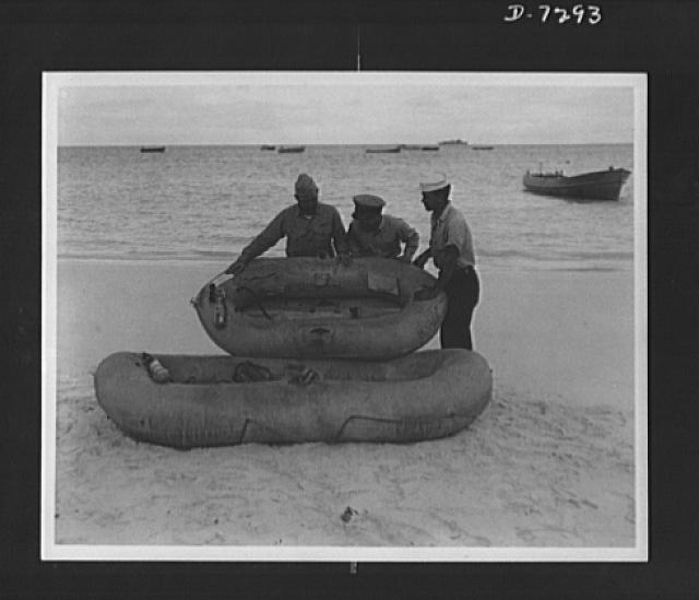 "Workers on Rickenbacker rescue boat. How mileage rationing can save lives on the battlefronts was pointed up dramatically by Captain Eddie Rickenbacker, who with six members of his crew were rescued after three weeks adrift on life rafts in the Pacific. ""One tire that is not wasted on pleasure driving may save the lives of seven men as ours was saved,"" Rickenbacker said. One old rubber tire is sufficient to make a three-man raft of the type that saved the party in the Pacific"