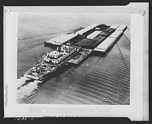 War materials. Oil, merchandise freight, and other covered cargo, probably cotton, move up the broad Mississippi ahead of a powerful towboat