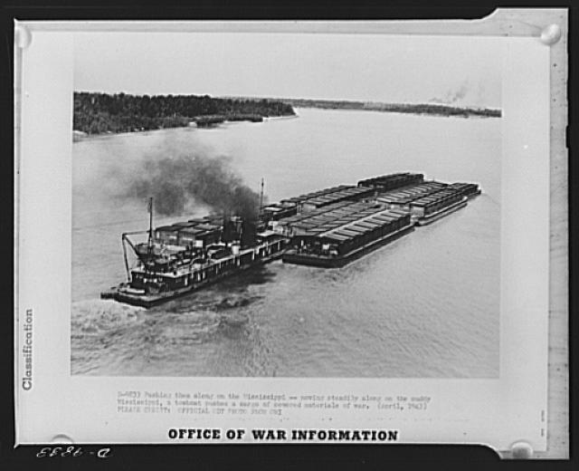 Pushing them along on the Mississippi. Moving steadily along the muddy Mississippi, a towboat pushes a cargo of covered materials of war