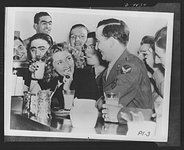 Joan Blondell eats with the boys at a North Atlantic base while on a United Service Organization (USO) camp show tour
