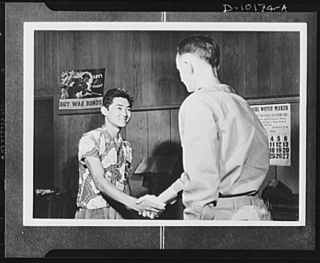 "Japanese-American volunteers. First of the territory's quota of 1,725 AJA (Americans of Japanese ancestry) volunteers to be inducted into the U.S. Army Combat Regiment now being formed, 18-year-old Mitsura Doi of Kauai, Hawaii, garage worker, receives congratulations from Major Charles V. McManus, adjutant of the Kauai Service Command who administered the oath of induction at 2:40 PM, Thursday, March 11. Doi was born at Koloa and volunteered with the blessing of his parents. ""I'm just waiting to begin training and get into action,"" he said as he shook hands with Major McManus"