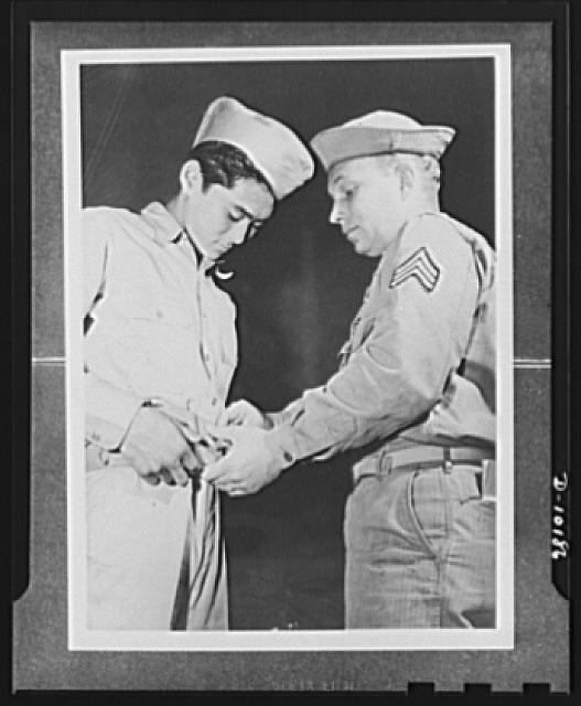 Japanese-American volunteers. First AJA [Americans of Japanese ancestry] volunteer to put on the uniform of the U.S. Army, Mitsuru Doi, eighteen, of Lihue, Kauai, is shown how to buckle on his ammunition belt. Doing the showing is Sergeant John H. Chynoweth, acting first sergeant of the provisional company of Kauai inductees, and nephew of the Brigadier General Chynoweth who was recently awarded the Distinguished Service Medal for his activities in the Philippines even after occupation of the islands by the Japanese