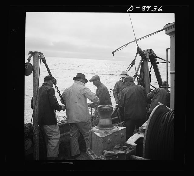 Victory food from American waters. At sunset fishermen mend nets torn by rocks on the ocean floor. A shortage of linen twine and Manila hemp needed for nets is only one of the war-time difficulties fishermen today must face