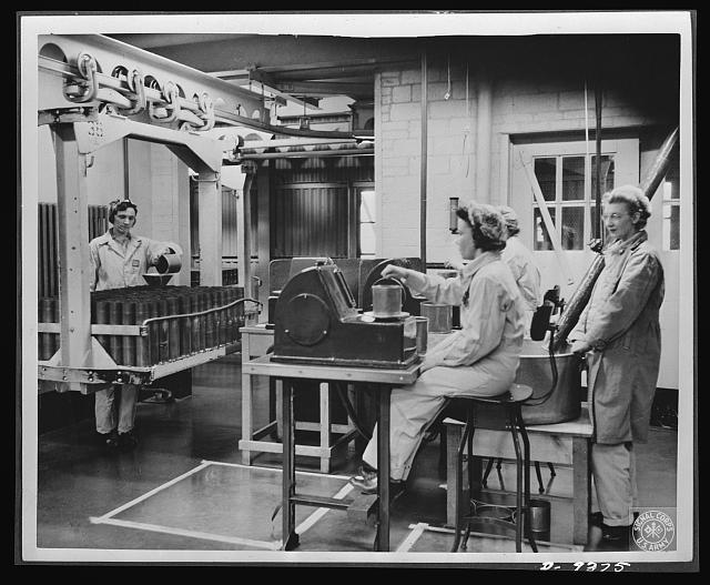 Production. Shell loading. Weighing the propelling charges of smokeless powder before they are poured into shells at a large Midwest loading plant. This precise work is done mostly by women. Mechanical devices produced in the fuse division enable soldiers in the field to delay or accelerate the explosion of a projectile. Ravenna ordnance plant