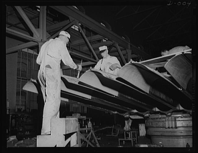 Torpedo tubes get coat of paint. Painters putting the finishing touches on torpedo tubes in production at an eastern Navy arsenal. All kinds of skilled workers are needed in the expanded war program. Production has been stepped up in this and ten other arsenals throughout the country
