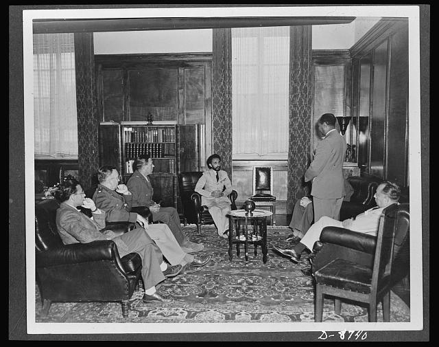 American military delegation calling on Haile Selassie. In conference with the American delegation. Left to right: F. N. Plangin, Office of War Information (OWI); Lieutenant Colonel Robert M. Baughey; Colonel Edwin Clark; His Majesty, Haile Sellassie, Emperor of Ethiopia; Taffarra Worq (standing), and George Strompl. These picture are the first to be taken for publication since His Majesty's return to become a fighting member of the United Nations