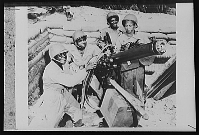 U.S. troops on guard in the New Hebrides. A U.S. Army gun crew, mans a heavy machine gun at a defense employment in the New Hebrides, where British, French and American forces are engaged in joint operations against the Japanese