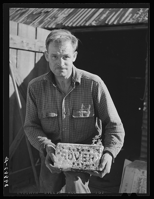 Miner with gold and silver brick worth about 2,000 dollars. El Dorado Canyon, Clark County, Nevada