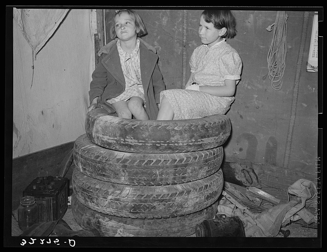 Daughters of white migrant auto wrecker sitting on tires in corner of tent home. Nueces Bay, Corpus Christi, Texas