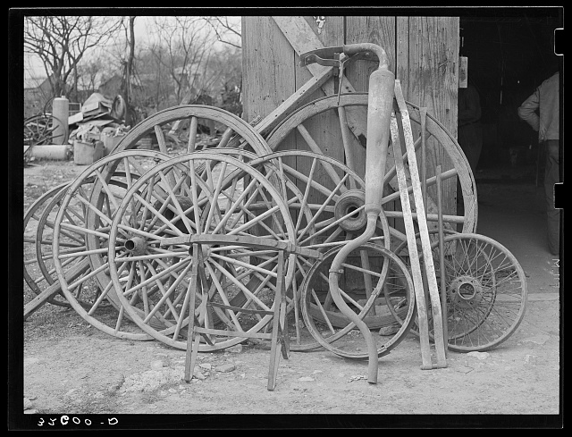 Wagon wheels and automobile exhaust pipes in front of blacksmith shop. San Antonio, Texas