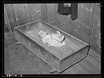 Baby of family living on relief. Notice the homemade cradle. Near Jefferson, Texas. Housing conditions in this section are particularly bad