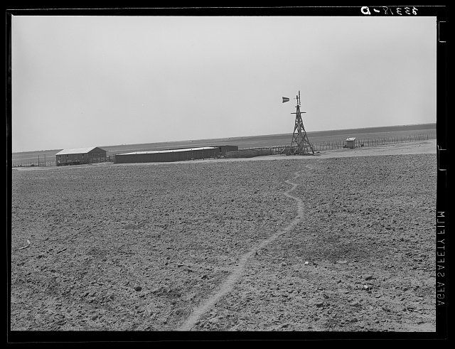 Windmill and hog pen and shed on large 4900 acre farm near Ralls, Texas. Path leads through fields from day laborers' homes