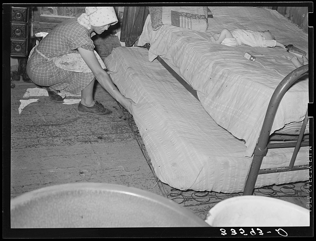 Wife of tenant farmer pulling out trundle bed in her one-room shack home near Sallisaw, Okahoma