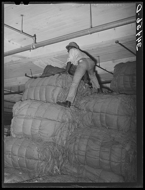 Warehouse worker atop stack of burlap bags. Compress at Houston, Texas