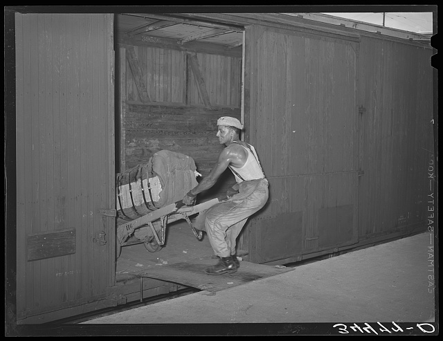 Negro unloading bale of cotton from railroad car. Compress, Houston, Texas