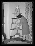 Wife of local merchant arranging bric-a-brac in her home. Concho, Arizona