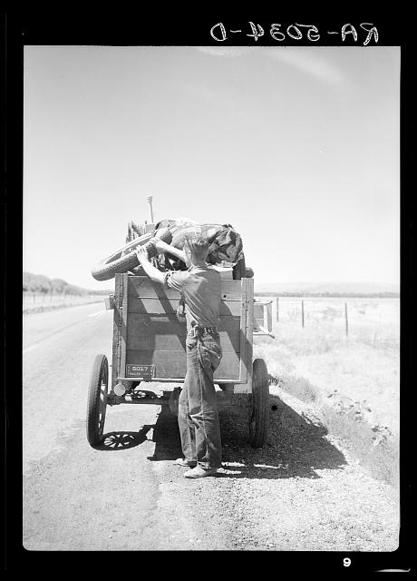 Drought refugees from South Dakota on highway making sure that nothing falls off the trailer to the Pacific Coast. Montana