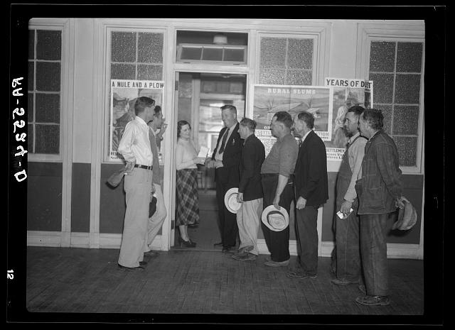 Resettlement clients arrive at the Resettlement Administration office after tobacco sale to make payments on their loans. Kinston, North Carolina