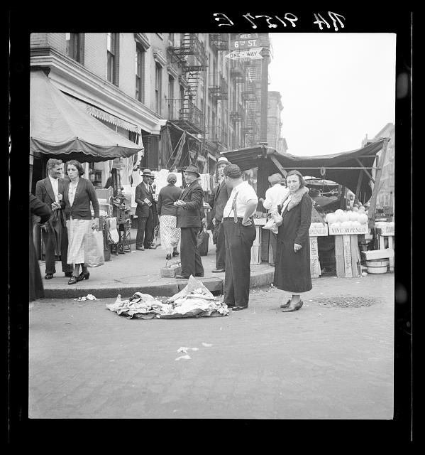 Background photo for Hightstown project. Sixth Street and Avenue C, New York City, where the Solomon family do their shopping. In the street and displayed on newspaper. All socks for sale at ten cents the pair
