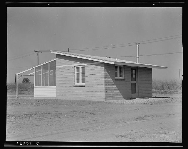 "One of forty houses adjoining Arvin (Kern County) camp for migrants, California. These houses are built for and rented to migratory agricultural labor by Farm Security Administration. This house is designed to represent ""one step up from the tent"""