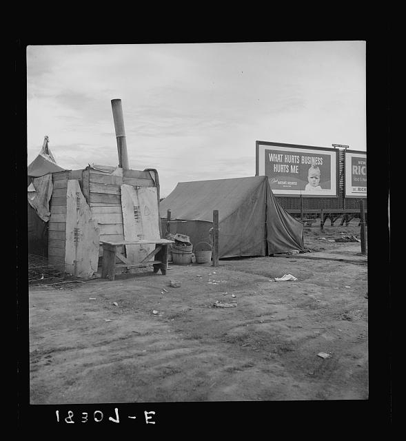Squatter camp on the flat where families live during the orange picking season. Near Porterville, California