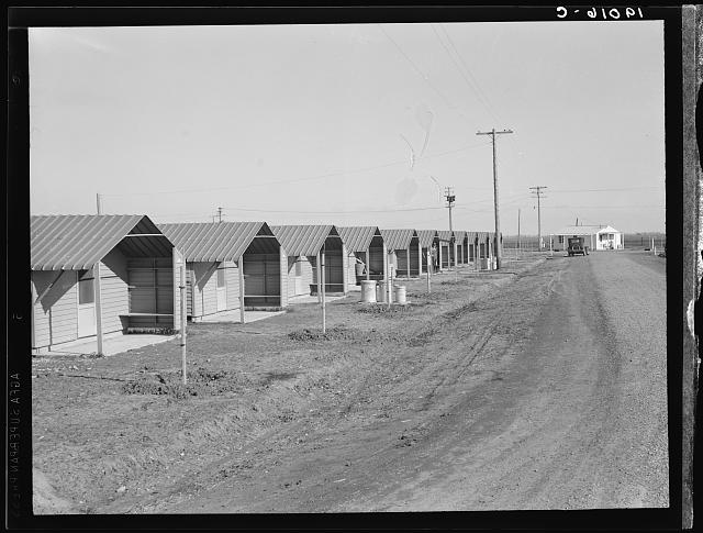 United States government camp for migratory workers, (Farm Security Administration-FSA), Westley, California. Pre-fabricated steel shelters replace the use of tents and tent platforms in this newly constructed camp. Camp manager's house at end of avenue