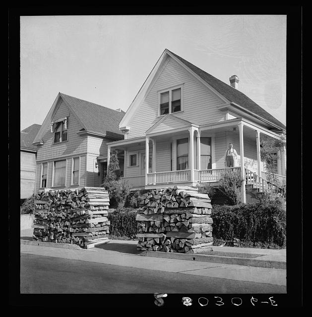 Woodpiles along the street are a characteristic of Portland, Oregon. Costs five dollars and fifty cents per cord, and must be hauled thirty-five miles. (Shows homeowner on porch.) Portland, Oregon