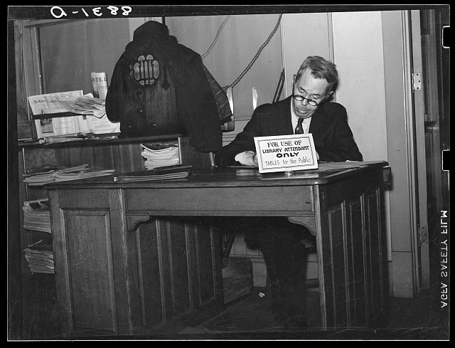 Attendant in newspaper reading room of public library. Omaha, Nebraska