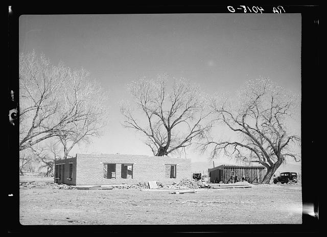 New adobe house. Temporary house in background. Bosque Farms, New Mexico