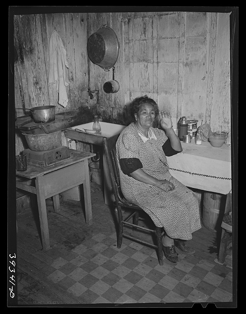 Mexican woman at table in kitchen of her two-room house. San Diego, California