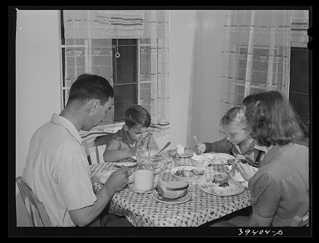 Marine sergeant and his family in the dining room of his home at the Navy defense housing for Navy and Mareines and some defense workers. San Diego, California