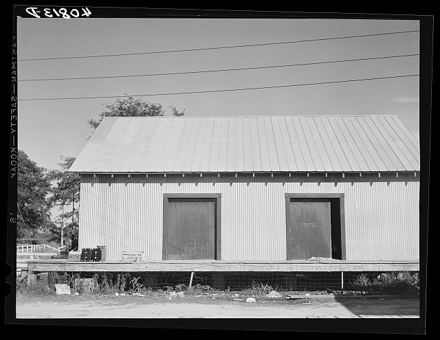 Warehouse that provides housing for a number of migratory agricultural workers. On the left is the baggage of some of the new arrivals. Camden, North Carolina
