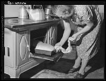 Mrs. Knees at oven, baking bread to be sold at farmers' market. Du Bois, near Penfield, Pennsylvania