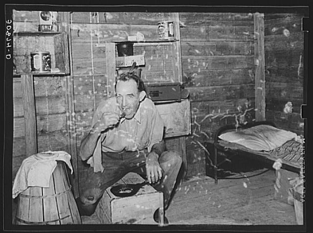 Migrant agricultural worker from Tennessee, formerly a railroad man, eating dinner in his shack, an old tool house. Homestead, Florida
