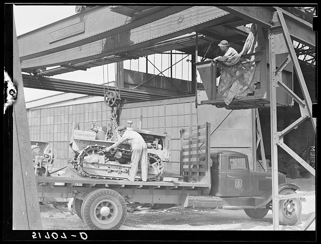 Hooking shepard crane to tractor preparatory to hoisting it off truck to repairs shop in FSA (Farm Security Administration) warehouse depot. Atlanta, Georgia
