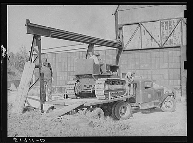 Repaired tractor being loaded from bank to truck ready to leave FSA (Farm Security Administration) warehouse depot in Atlanta, Georgia