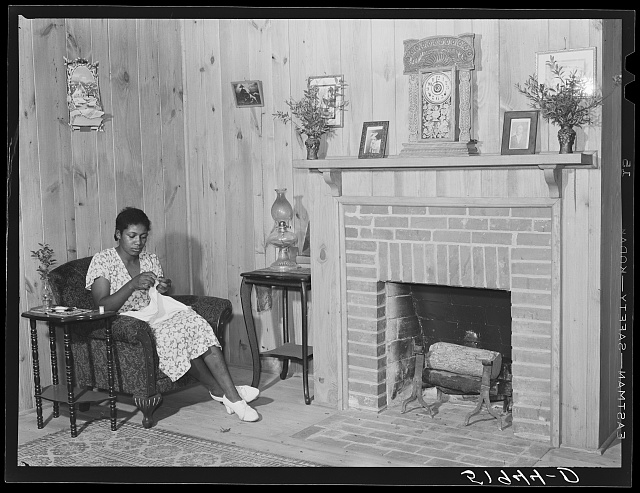 Daughter of Frederick Oliver, tenant purchase client, sewing in living room of new home. Summerton, South Carolina