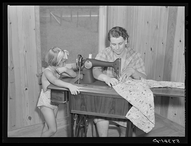 One of the project women making clothes for her family on her new sewing machine. Terrebonne Project. Schriever, Louisiana