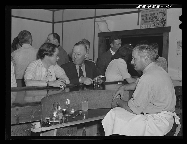 Mrs. Lyman Brewster talking with an acquaintance at the bar in Birney, Montana