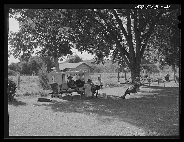 Guest resting on the lawn with Mrs. Jack Arnold at Quarter Circle U Ranch. Birney, Montana