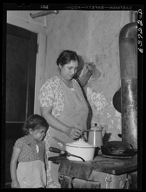 Wife and child of Mexican sugar beet worker in community kitchen, in one of the houses at Saginaw Farms, a FSA (Farm Security Administration) project