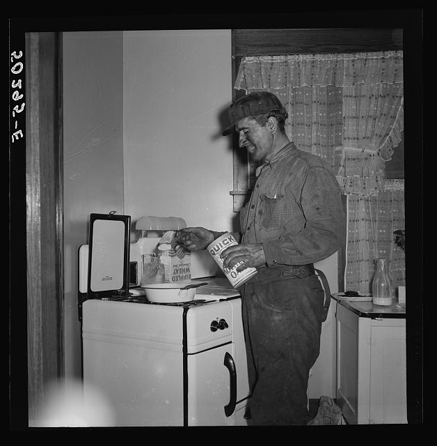 A more well-to-do miner starts his breakfast when he comes home in the morning after working on the night shift. He is Polish, his wife Hungarian. Westover, West Virginia