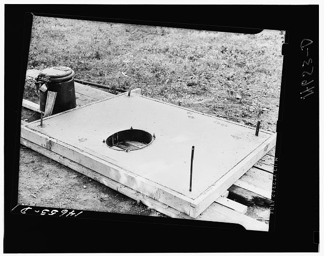 Concrete slab for sanitary privy. The stool at the left bolts on to the collar. The building is fastened to metal strips at corners. Minnesota