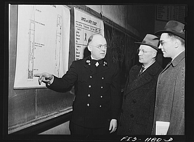 Fire department official in a small Minnesota town instructing Swedish-American civilian defense firespotters with a diagram of an incendiary bomb