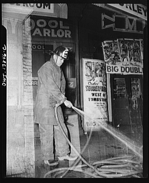Firehouse Station No. 4. Washington, D.C. Young fireman, a graduate of Dillard University in New Orleans, cleaning the hose after a small blaze
