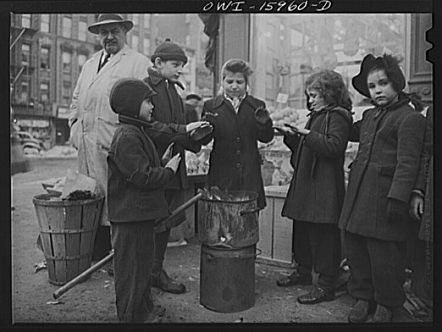 New York, New York. Italian-American children warming their hands outside a fruit store at First Avenue and Tenth Street